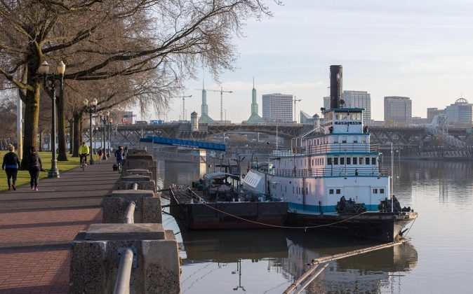 The twin towers of the Oregon Convention Center, site of the 2018 ADI Conference, break the Portland skyline behind the Sternwheeler Portland, which houses the Oregon Maritime Museum and is berthed along the Tom McCall Waterfront Park on the Willamette River.