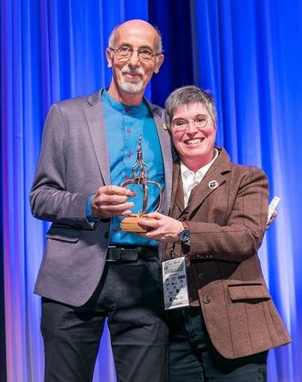 Master Distiller and Blender Hubert Germain-Robin, left, receives the lifetime achievement award for his contribution to the art of distilling from Nancy Fraley.