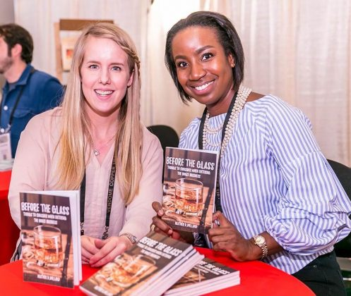 Author Heather Dolland, right, talks with Lacie Thornton, of Grand Traverse Distillery, during a book signing at the White Mule Press booth.