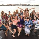 Liz Henry, center in purple, enjoys the Pontoon Porchboat Outing with the Spirited Women, a group formed from the bartending community in Madison, WI. These gatherings have raised money for charitable causes, including the local Rape Crisis Center and Safer Bar Training.