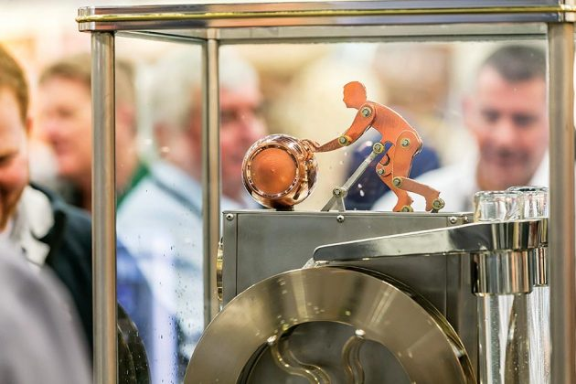A mechanical man rolls a barrel inside the spirits safe on a still at the Vendome Copper and Brass Works booth on the vendor expo floor.