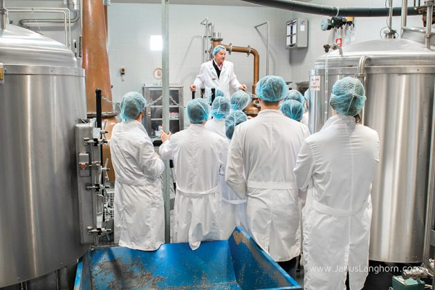 With an emphasis on cleanliness, Henric Molin, center, leads a tour group in lab coats and hair nets, through a tour of the distillery.
