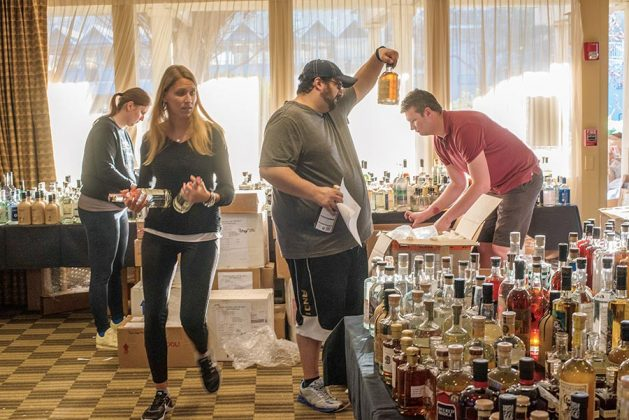 Left to right, Sorting of the spirits begins five days before the judging, with opening of the boxes. Left to right, Veronika Karlova, Claudia Bailoni, Justin Koury and Joe Barber begin sorting spirits into classes, categories, sub-categories, flights, and then order within each flight.